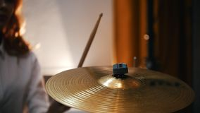 Repetition. Redhead girl plays on drums plates . slow motiom vibration. Backlights.