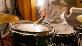 Repetition. Redhead girl plays on drums in the studio. Focus on drums. Mid shot stock images