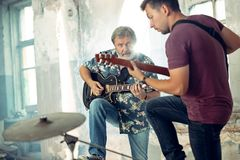 Repetition of rock music band. Electric guitar players. Repetition of rock music band. Bass guitar player, electric guitar player at loft. Rock music and jam stock images