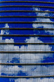 Repetitive horizontal louvers and reflective sky. Exterior facade with multiple repetitive horizontal louvers and windows reflecting a blue sky with clouds Stock Images