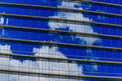 Repetitive horizontal louvers and reflective sky. Exterior facade with multiple repetitive horizontal louvers and windows reflecting a blue sky with clouds Royalty Free Stock Photos