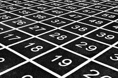 Repetitive pattern of numbers on a playground create an optical illusion. stock images