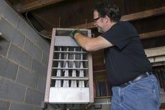 Repirman che pulisce condotta superiore della fornace di gas Fotografie Stock Libere da Diritti