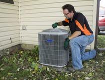 Repirman che stringe lo schermo del fan sull'unità esterna di Conditiong dell'aria Immagine Stock