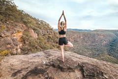 Repisa femenina del acantilado de la montaña del asana de la balanza de la yoga de la fuerza imagen de archivo libre de regalías