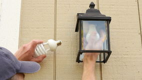 Replace Old Bulb with CFL. Man outside changing an incandescent light bulb to a CFL light bulb in a light fixture to save energy stock footage