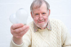 Replace old light bulbs. An image of a Senior holding two old low efficiency light bulbs prior to disposal and replacement. A concept image of the message ' Royalty Free Stock Photography