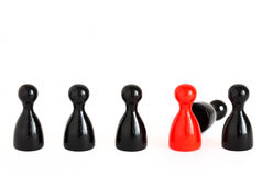 Replacement III. A row of black game figurines with a red one symbolizing the replacement of one royalty free stock photo