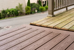 Replacement of old wooden deck with composite material. Repair and replacement of an old wooden deck or patio with modern composite plastic material Stock Image
