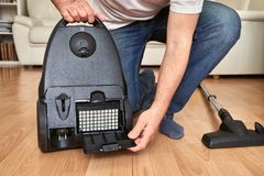 Replacing an air filter in vacuum cleaner at home. Stock Photo
