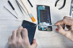 Replacing broken glass on a mobile phone in a mobile phone service royalty free stock photography