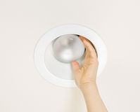 Replacing Burned Out Flood Light in Ceiling Mount Stock Photography
