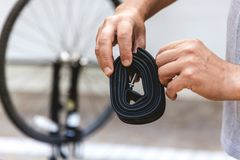 Cyclist hands are holding collapsed rubber bicycle camera stock image