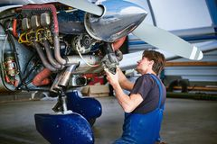 Replacing the defective parts of the aircraft service worker. Removal and repair of an engine starter of an airplane by a service worker stock photography