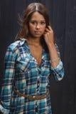 Replacing her hair. Twenty something beautiful girl wearing a low cut plaid shirt replacing her hair Stock Photos