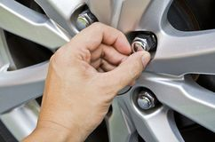 Replacing lug nuts by hand. Royalty Free Stock Photo