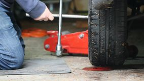 Replacing nuts on an old tire with lug wrench. Man replacing nuts on tire stock video