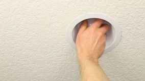 Replacing Old Lightbulb with CFL. Hand of a man changing an old incandescent light bulb with a newer daylight white compact fluorescent lightbulb to save energy stock video footage