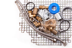 Replacing old plumbing. Water connection, clamp, linen and iron grid on a white background Royalty Free Stock Photography