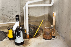 Replacing the old sump pump in a basement. With a new one to drain the collected ground water from the sump or pit Royalty Free Stock Images
