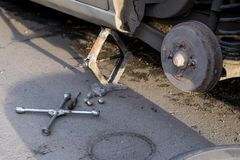 Replacing the rear wheel of the car. The car is mounted on the Jack. On the road lie screws, tool and wheel. Replacing the rear wheel of the car. The car is royalty free stock photography