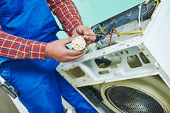 Replacing water level pressure sensor of washing machine. Washing machine repair. Repairer hands replasing with water level sensor pressure switch in front of stock images