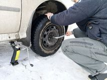 Punched and flat tire on the road. Replacing the wheel with a jack by the driver stock image