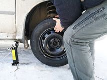 Punched and flat tire on the road. Replacing the wheel with a jack by the driver stock photography