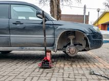 Replacing the wheel on the tire service center. Car without a wheel lifted on the jack. Replacing the wheel on the tire service center. Black car without a wheel stock image