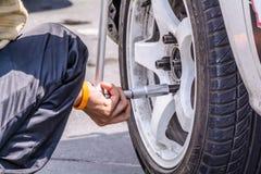 Replacing wheel vehicle. Mechanic technician worker replacing wheel vehicle of automobile at repair service station Royalty Free Stock Image