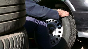 Replacing the wheels at the Tyre Services. Zrenjanin;Serbia;11.01.2016.Auto mechanic in car service mounted tire on the car stock footage
