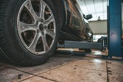 Replacing winter tires on summer tires in a professional garage with the help of professional tools. car on a hydraulic royalty free stock photos