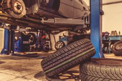 Replacing winter tires on summer tires in a professional garage with the help of professional tools. car on a hydraulic. Replacing winter tires on summer tires stock photography