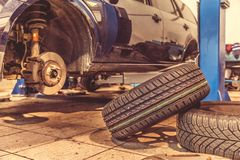 Replacing winter tires on summer tires in a professional garage with the help of professional tools. car on a hydraulic. Replacing winter tires on summer tires stock image