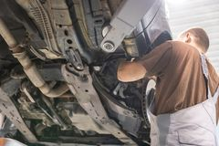 Repair and check car in repair shop. An experienced technician repairs the faulty part of the car. I change tires royalty free stock photo