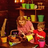 Replanting concept. Mother and son replanting flower in new pot. Mother and child replanting houseplant in black soil or. Dirt. Preparation for replanting stock image