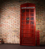 Replica iconic British telephone booth. Standing against a brick wall with a telephone sign and crown on the front Royalty Free Stock Photos