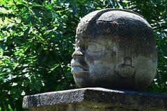 Replica of Olmec round stone head statue on pedestal stock image