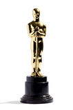 Replica of an Oscar award. Golden replica of an Oscar film award on a black plinth isolated on white in vertical format royalty free stock image