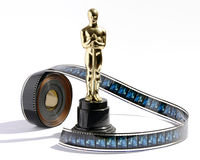 Replica Oscar statue with a roll of movie film. Replica golden Oscar statue on a black plinth standing on a white background with a roll of movie film royalty free stock photos