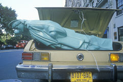 Replica of Statue of Liberty inn trunk of car with NY license plates Royalty Free Stock Photo