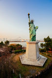Replica Statue of Liberty in Odaiba. Replica Statue of Liberty in Odaiba, with the Rainbow Bridge behind it Royalty Free Stock Images