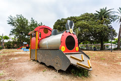 Replica train in the park. Large fixed red, yellow and silver replica train in the park for children to play on, background of trees and sky Stock Images
