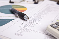 Report. With a ballpoint pen and a calculater on top with a chart diagram in the background Royalty Free Stock Photo