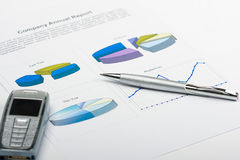 Report. Pen and phone laying on report with diagrams Royalty Free Stock Images