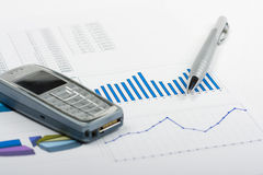 Report. Pen and phone laying on report with diagrams Stock Photography