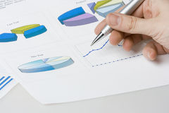 Report. Hand pointing on report with diagrams Stock Images