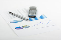 Report. Pen and phone laying on report with diagrams Royalty Free Stock Photos