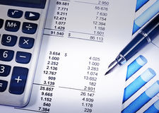 Report with blue pen and calculator Royalty Free Stock Photo