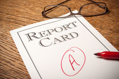 "Report card on a desk. Report card on an oak desk with a red ""A"" written on it . A red pen in the foreground and glasses in the background Stock Photography"